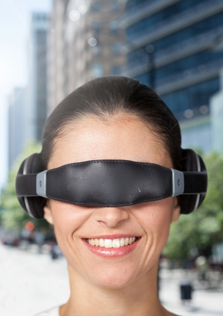 Woman using virtual reality glasses against city buildings in background