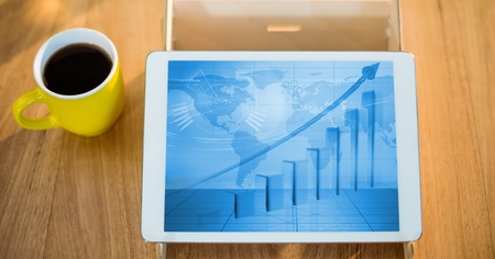 Digital tablet with graph chart on wooden table