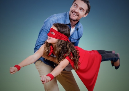 Digital composition of dad carrying his daughter in superhero costume against green background