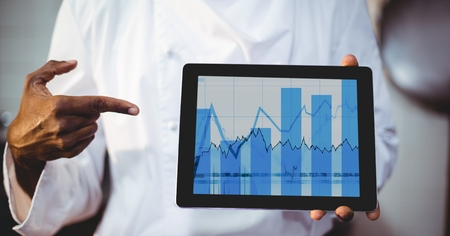 Mid section of man showing digital tablet displaying graph chart on screen