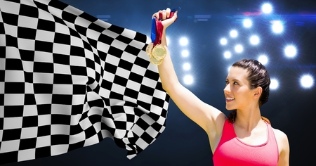 Composite image of athlete holding medals against checkered flag in stadium