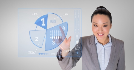 cropped: Business woman touching digitally generated pie chart against grey background