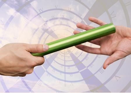 Hand van atleten die tijdens het relaisrace tegen de digitaal gegenereerde klok de knuppel overlaten