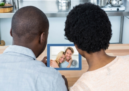 Couple having video call with friends on digital tablet at home