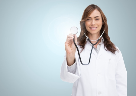 light brown hair: Portrait of doctor examining with stethoscope against grey background