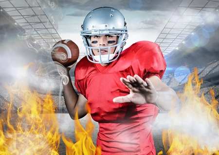 Digitally generated of athlete playing american football between the fire flame Stock Photo
