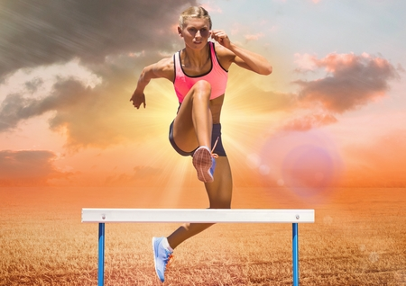 Digital composition of athlete jumping over hurdles against sky in background