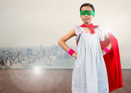 Portrait of super kid in red cape and green mask standing with hand on hip against digitally composite cityscape Stock Photo