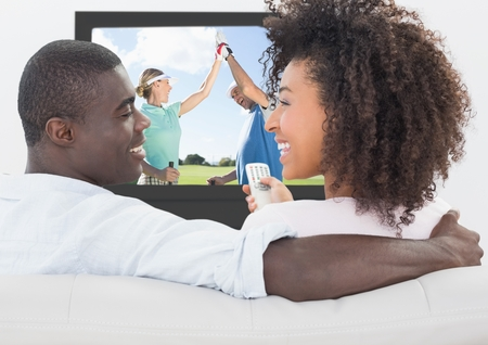 Couple smiling while watching golf on television at home