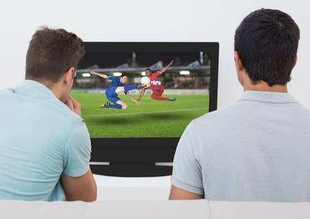 opposing: Rear view of men watching football match on television at home
