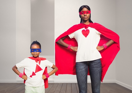 Mother and daughter in superhero costume standing with hands on hips at home Stock Photo