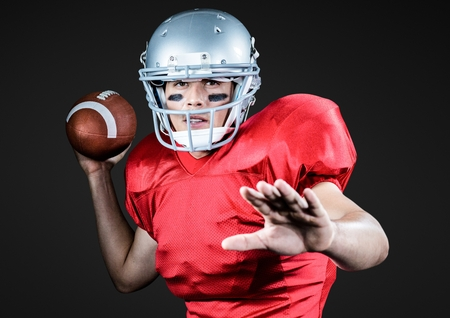 Portrait of athlete playing american football against black background