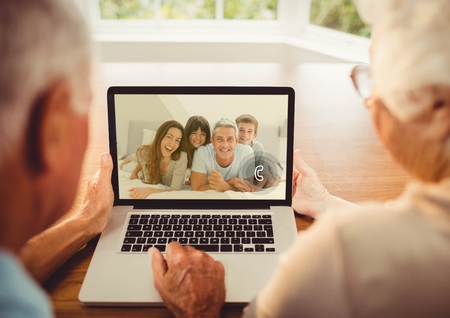 Rear view of senior couple having a video call with their family on laptop Stock Photo
