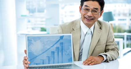 Portrait of smiling businessman showing graph on laptop in office