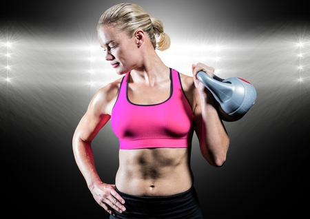 Athlete with hand on hip holding kettlebell against digitally composite background