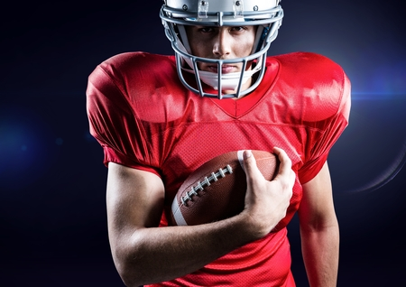 American football player holding rugby ball against blue background Stock Photo