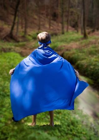 Digital composite of kid in blue cape standing in field