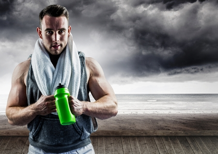 Digital composite of muscular man standing with sipper water bottle against storms clouds