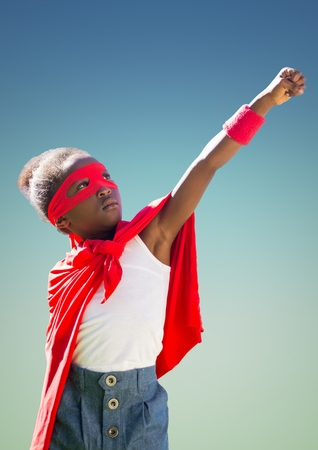 Kid in red cape and mask standing with fist against turquoise background