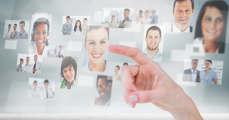 hooded: Digital composite of hand touching profile picture of business people Stock Photo