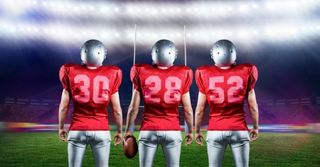 business pitch: Digitally generated of american football players standing with rugby ball in stadium
