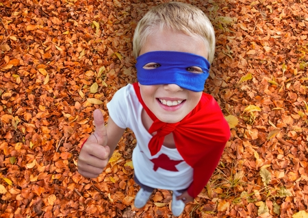 dedicate: Composite image of smiling kid in red cape and blue mask showing thumbs up during autumn