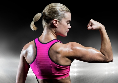 Fit woman flexing muscles against digitally generated background Stock Photo