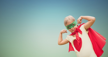 Composite image of kid wearing red cape and green mask showing muscles against clear sky