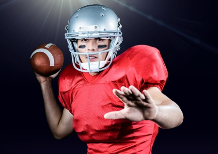Portrait of American football player throwing ball against black background Stock Photo