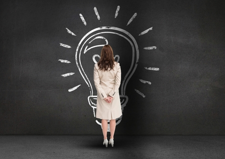 hand on chin: Digital composite of businesswoman looking at innovative bulb on grey background