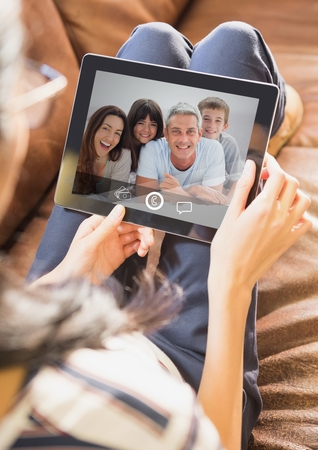girl lying studio: Woman sitting on sofa having video call with family on digital tablet at home