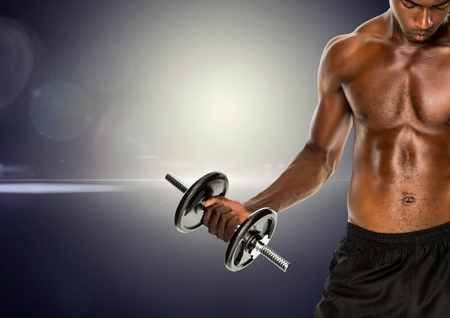Serious fit man lifting dumbbell standing against digitally generated background