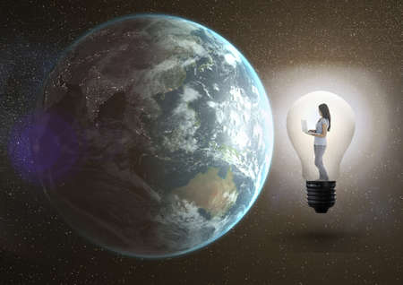 wobbly: Digital composite image of a girl using laptop in the electric bulb besides earth