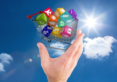 tablet pc in hand: Digital composite image of man hand holding a shopping cart against sky background