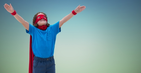 Smiling boy wearing superhero costume standing with arms outstretched against sky blue background Stock Photo