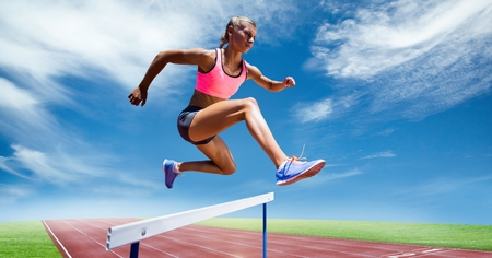 scrolling: Digital composite image of female athlete jumping above the hurdle against sky background