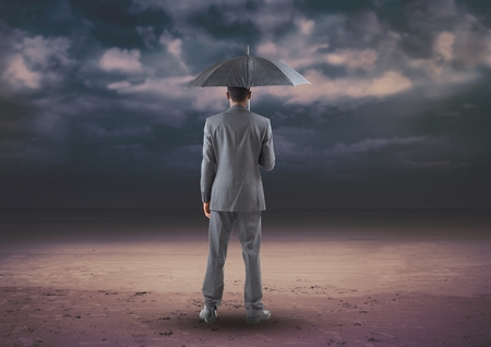 Rear view of businessman standing with umbrella against digitally generated background Stock Photo