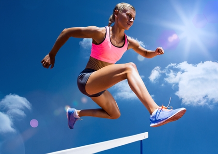 Female athlete jumping above the hurdle against sky background