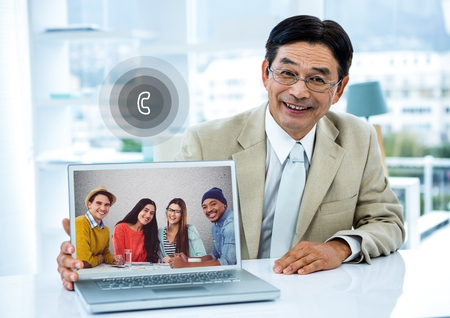 Portrait of smiling businessman having video call with colleagues on laptop in office Stock Photo