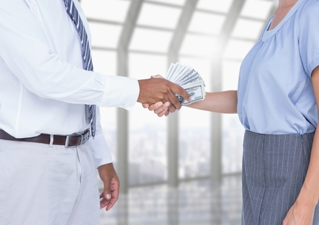 Businessman bribing partner while shaking hands�in office