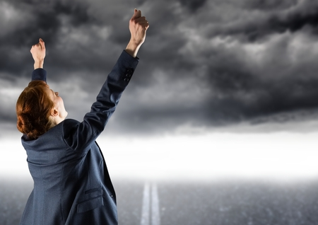Digital composite image of excited businessman crossing the finish line against storm clouds Stock Photo