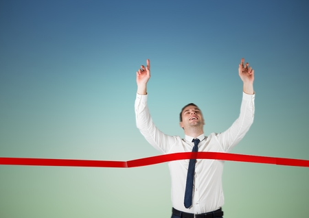 Businessman crossing finish line with arms up against colored background Stock Photo