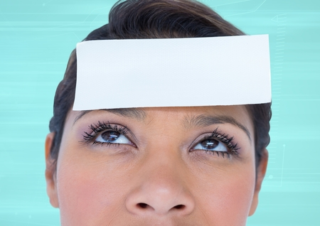 Blank note on a woman forehead against turquoise background