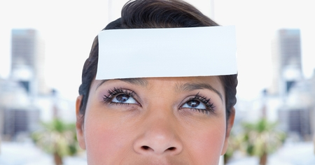 Woman with post it reminder note on forehead against blurr background Stock Photo