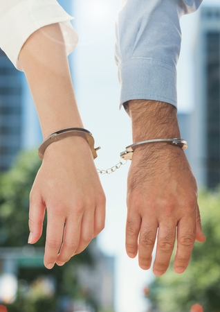 Businesspeople handcuffed together against blurr background