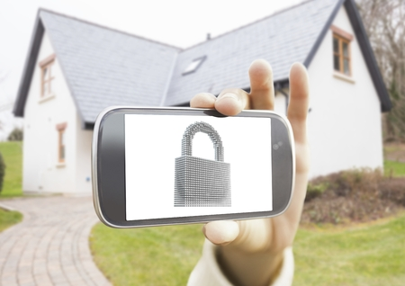 Close-up of hand holding mobile phone with lock on screen against houses in background Stock Photo