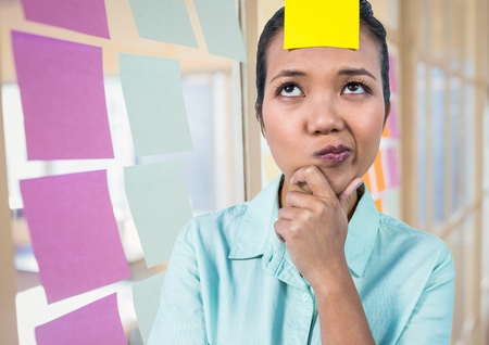 Blank sticky note on female executive forehead in office Stock Photo