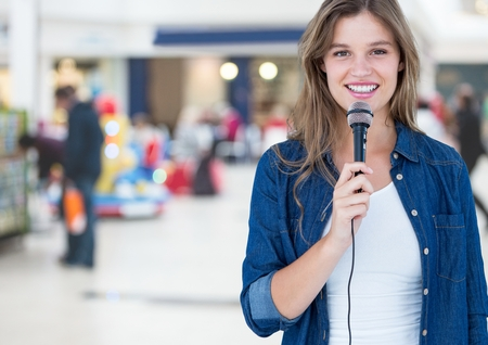 Woman speaking on microphone against blurr background