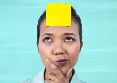 Frustrated businesswoman with sticky note stuck on her forehead against blue background Stock Photo