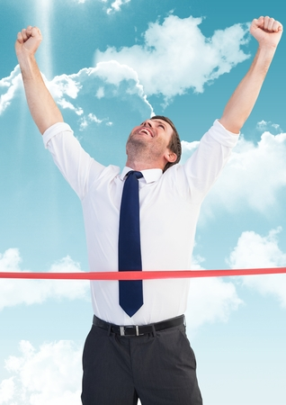 Digital composite image of businessman crossing finish line with arms up against sky and cloud Stock Photo